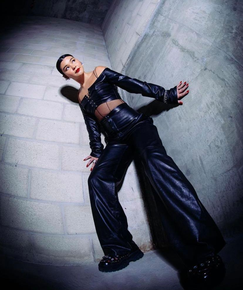 Audrey Mika posing against the wall in a leather two piece outfit