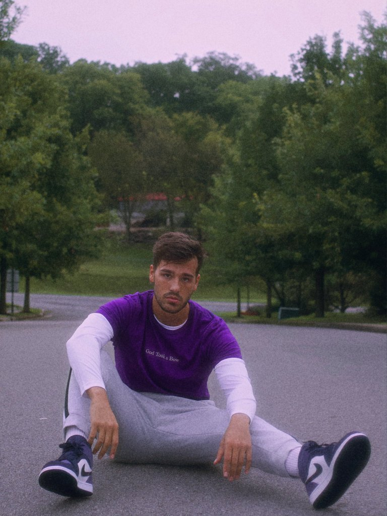 Jacob sitting in the street in a purple shirt