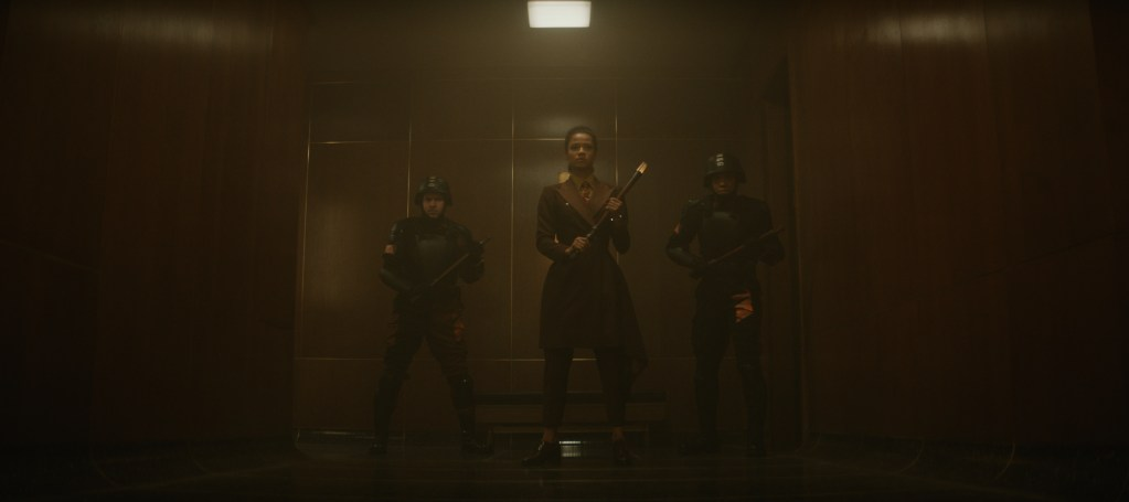 Judge Renslayer (Gugu Mbatha-Raw) and two guards stand at the end of a dark corridor.