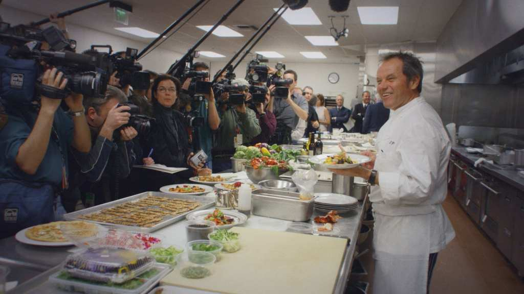 Wolfgang Puck in one of his restaurants with various cameras pointed at him
