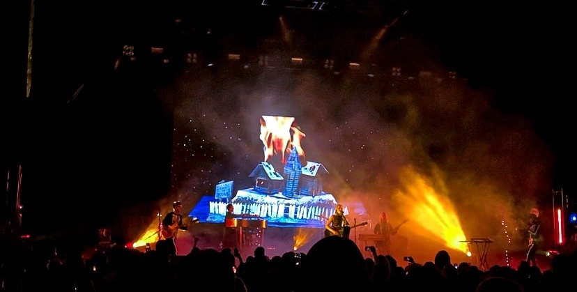 A house on fire scene as the backdrop for Phoebe Bridgers' performance at Leader Bank Pavilion in Boston, MA for The Reunion Tour.